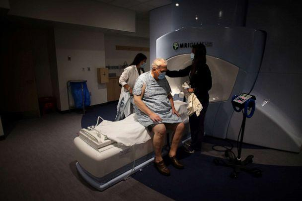 PHOTO: Radiation therapists Jessica Penny (left) and Jennifer Campbell (right) prepare a Kenton cancer patient for treatment at the Department of Radiation Oncology in Brigham and Women's Hospital in Boston, June 10, 2020 (Boston Globe via Getty Images)