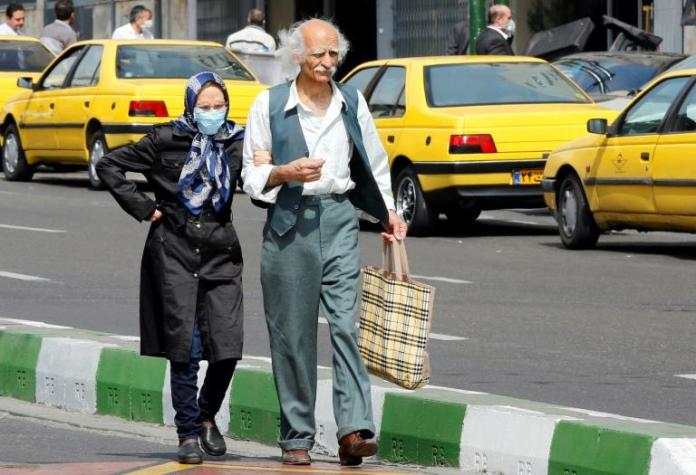 An elderly couple walk in the Iranian capital Tehran on March 15, 2020. Iranian President Hassan Rouhani has defended his administration's response to dealing with the spread of the coronavirus although it has not imposed a lockdown (AFP Photo/STRINGER)