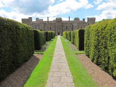 gardens with a path surrounded by hedge bushes leading to a castle