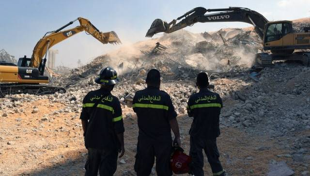 A rescue team watch diggers tackle the removal of debris from this week's massive explosion in the port of Beirut, Lebanon. AP