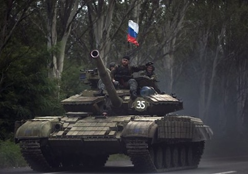 Pro-Russian rebels ride on a tank flying Russia's flag, on a road east of Donetsk