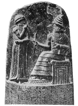 Hammurabi (standing) receiving his royal insignia. He's holding his hand over his face as a sign of prayer.