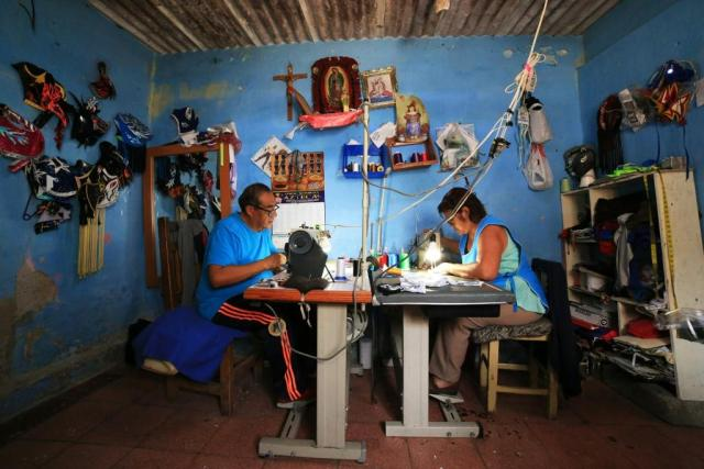 Jose Isaias Huerta (L), a former wrestler, and his wife, Virginia, manufacture lucha libre masks which people are using as face masks in the fight against coronavirus