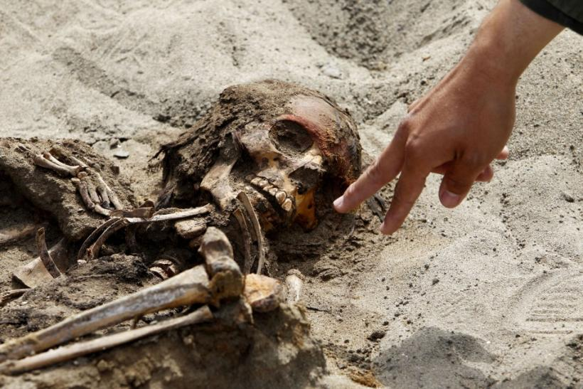 Archaeologist Oscar Gabriel Prieto points to the remains of a child, part of the 42 children and 74 camelids remains unearthed that were sacrificed approximately 800 years ago in the fishing town of Huanchaquito, Trujillo