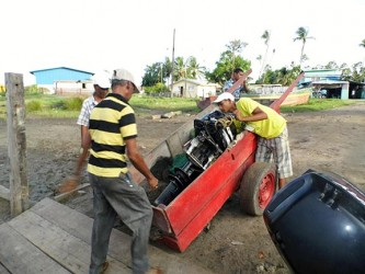 Many hands do light work: Transporting the engine from jetty to boat.  (Photo by Jannelle Williams)