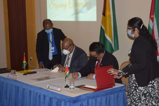 Public Works Minister, Juan Edghill (seated at left) and Suriname's Transport Minister Albert Jubithana signing the agreement yesterday. (Ministry of Public Works photo)