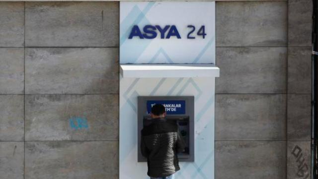 A man uses an ATM machine of Bank Asya in Istanbul