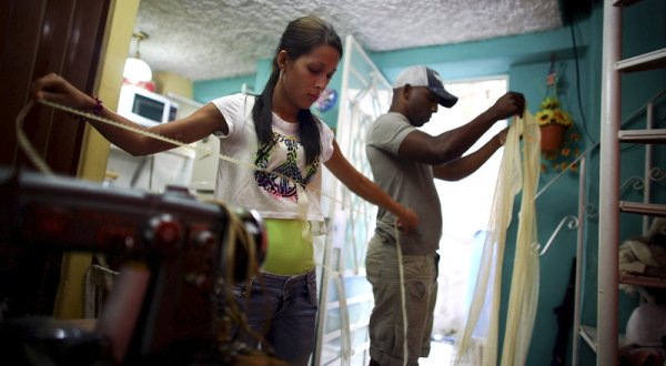 Cuban entrepreneur Barbara Fernandez Franco works in her home in Havana as her boyfriend Michel Perez Casanova helps. (Credit: David Gilkey / NPR)
