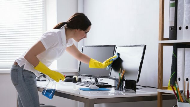 Woman Cleaning Computer Screen In Office, Terminating A Contract Concept