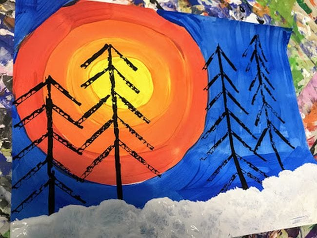 Painting of large yellow and orange sun on a blue sky with snow and bare black trees