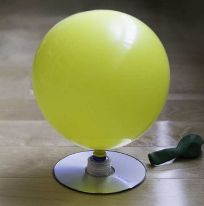 Inflated yellow balloon attached to a CD by a bottle cap