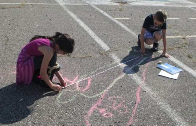 Fourth grade science students measuring their outlines drawn in sidewalk chalk on the playground