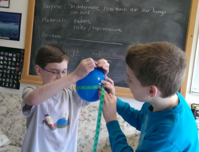 Two eighth grade science students measuring the circumference of a blue balloon
