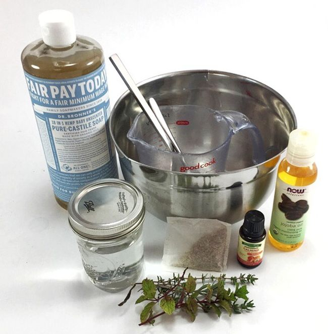 Mixing bowl with castille soap, jar of water, essential oils, and herbs