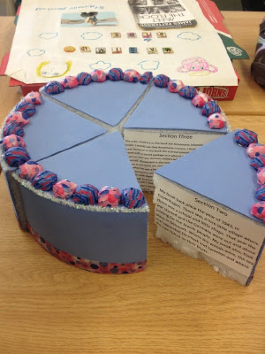 A purple birthday cake made out of a foam block and colored paper cut into wedges. On each wedge is a written paragraph.