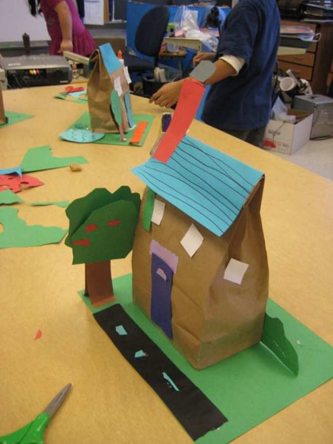 Paper lunch bag stuffed and turned into a house, sitting on construction paper lawn with a tree and road