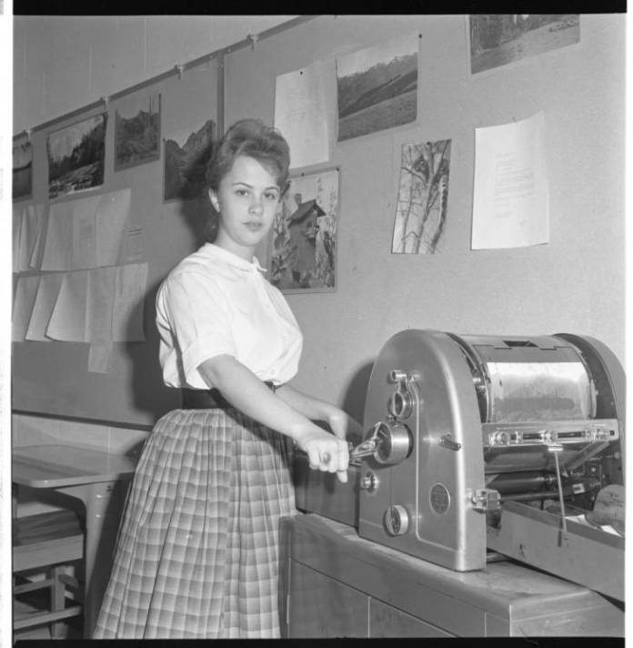 Black and white photo of a 50's teacher using a mimeograph machine -- teaching a long time