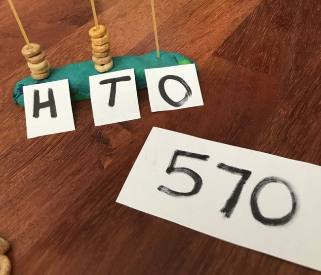 Uncooked spaghetti strands stuck upright into playdough and labeled H, T, and O with Cheerios stacked on each next to card reading 570