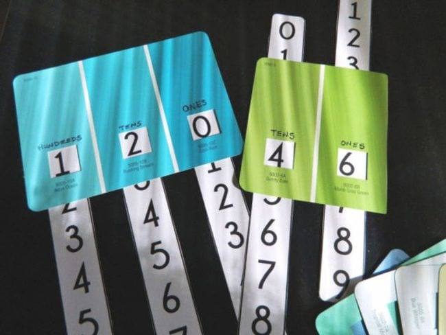 Colorful paint sample chips with individual sections labeled tens and ones, with number strips inserted (Place Value Activities)