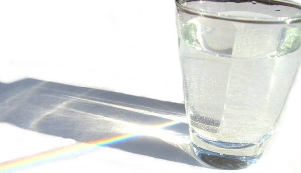 sunlight reflecting through a glass of water, creating a rainbow on the table behind
