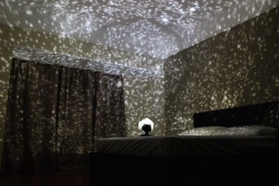 DIY classroom space themed wall projector casting stars in dark room
