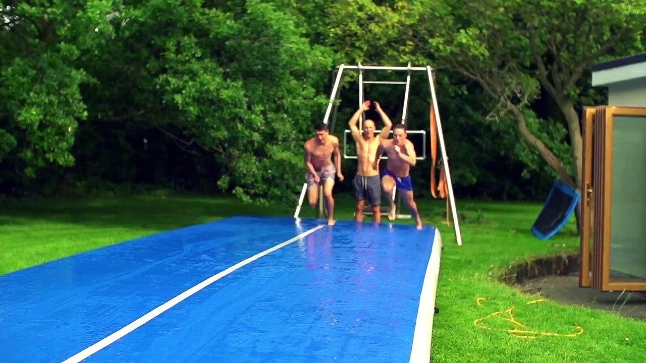des gars s amusent sur un tapis gonflable glissant et font des tricks
