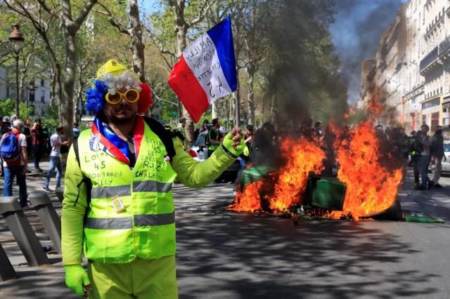 """Manifestante """"colete amarelo"""" acena bandeira da França durante protesto em Paris — Foto: Gonzalo Fuentes/Reuters"""
