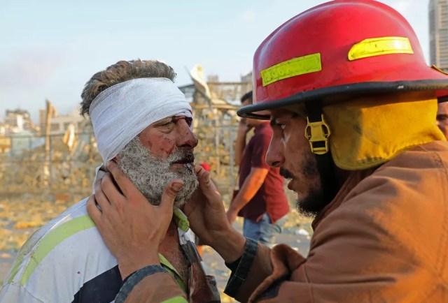 Homem ferido é examinado por um bombeiro perto do local da explosão em um porto de Beirute nesta terça (4) — Foto: Anwar Amro/AFP