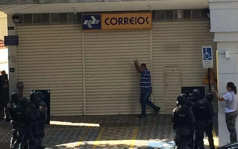 Refém deixa a agência dos Correios com as mãos para cima (Foto: Will Soares/G1)