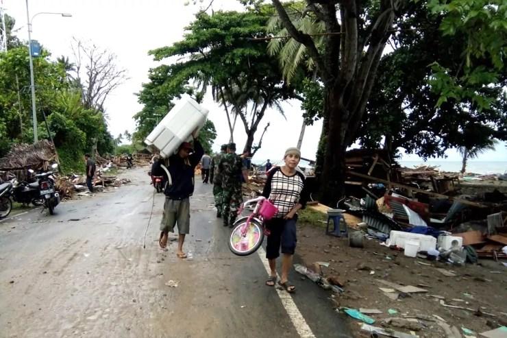 Moradores evacuam área destruída por Tsunami na praia de Carita  — Foto: Semi / AFP