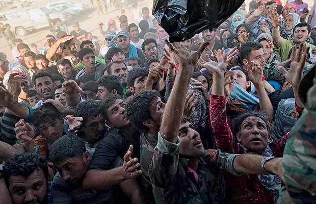 RESISTÊNCIA Sírios recebem comida no campo de Kawergost, no Iraque. Metade dos refugiados é formada por crianças (Foto: Lynsey Addario/The New York Times)