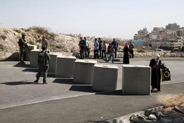 Palestino passa por verificação da identidade em bloqueio montado por forças de segurança israelenses. Polícia tenta conter onda de ataques com faca feitos por palestinos (Foto: Baz Ratner/ Reuters)