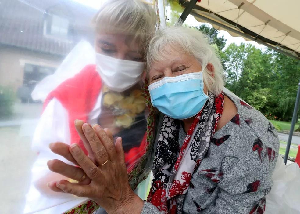 1º de julho - Idosa abraça diretora de casa de repouso na Bélgica — Foto: Yves Herman/Reuters