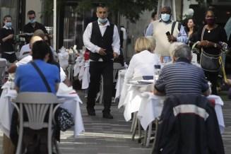 Pessoas jantam em mesas ao ar livre em Londres, na Inglaterra, na segunda-feira (21) — Foto: Kirsty Wigglesworth/AP