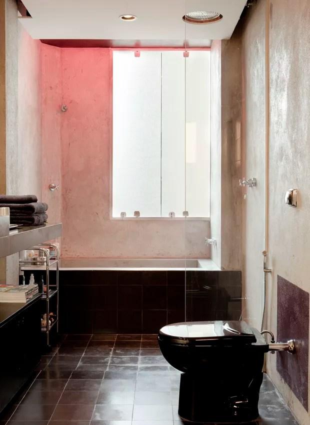 O designer de interiores Sandro Brasil economizou nos acabamentos de seu apartamento, mas criou efeitos de iluminação diferentes. A banheira de alvenaria com cimento queimado tem lâmpadas vermelhas, que transformam o banho em sessão de cromoterapia (Foto: Edu Castello/Casa e Jardim)