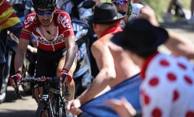 De Gendt, o ganhador da 12ª etapa, pedala na frente, cercado por dois daqueles fãs empolgadíssimos que ficam às margens das provas, em busca de contato com os ciclistas