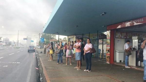 Na BR-101, em Natal, perto de onde os manifestantes atearam fogo em pneus, pessoas aguardam na parada a passagem de ônibus, que devem rodar com 40% da frota (Foto: Andrea Tavares/G1)