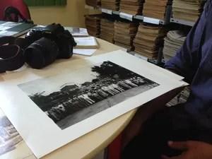 Luiz mostra algumas fotos antigas do seu acervo. Imagem revela a inauguração da Ponte Major Guapindaia, em 1948 (Foto: Gaia Quiquiô)