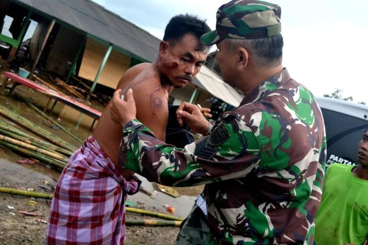 Na província de Banten, soldado examina morador que ficou ferido em tsunami  — Foto: Antara Foto/Muhammad Bagus Khoirunas/ via REUTERS