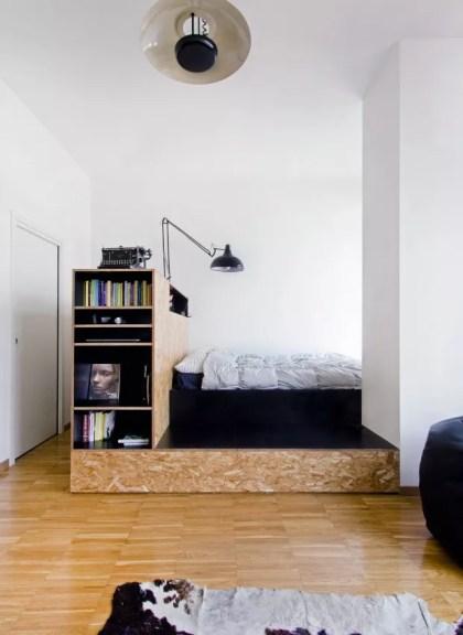 O uso do OSB trouxe uma interpretação bem atual para este apartamento. A estrutura que comporta a cama foi combinada a um laminado preto e, além de funcionar como cabeceira, também abriga livros (Foto: Francesca Perani / Divulgação)