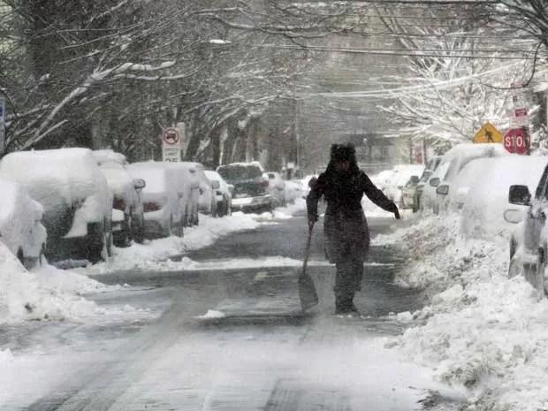 Mulher ajuda a retirar neve de uma rua em Jersey City, Nova Jersey. (Foto: Eduardo Munoz / Reuters)