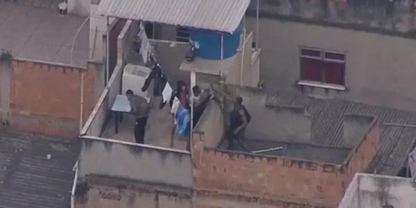 Homens armados tentam fugir durante operação da polícia em telhado no Jacarezinho, Zona Norte do Rio — Foto: Reprodução/TV Globo