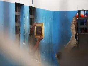 Presidiário usa um espelho para observar visitantes que adentram o Complexo Penitenciário de Pedrinhas, em São Luís (MA) (Foto: Mario Tama/Getty Images)