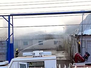 Bombeiros jogam água em tanque de diesel em área próxima a galpões que foram incendiados (Foto: Ricardo Moreira/G1)