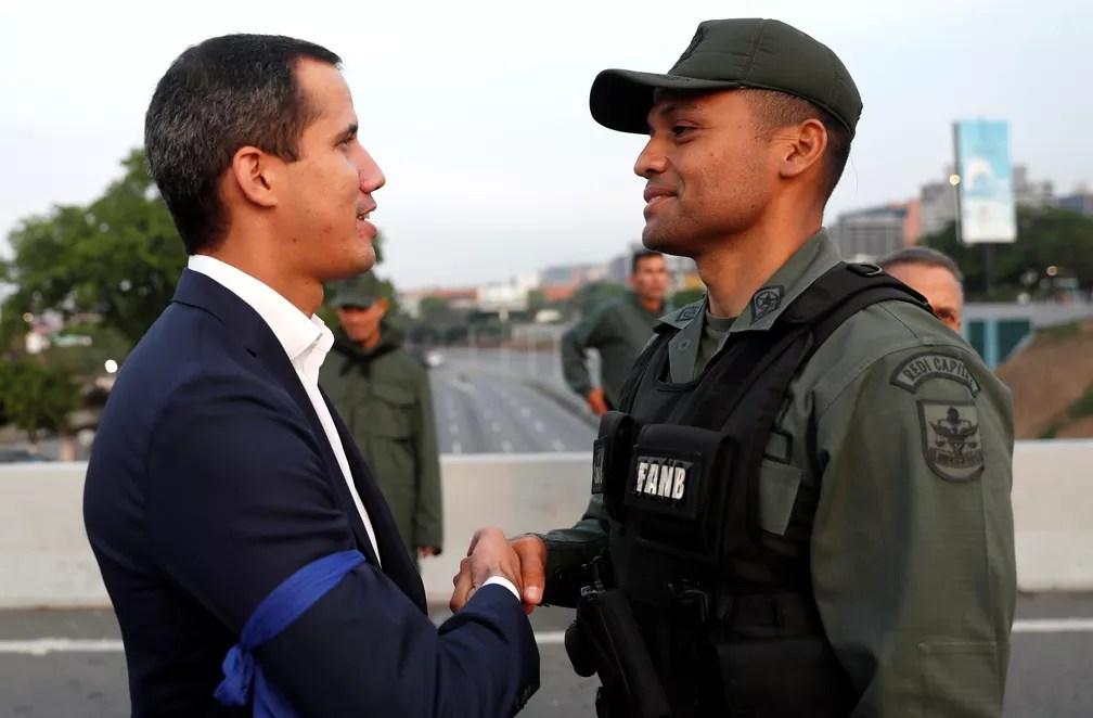 Juan Guaidó cumprimenta um militar perto da base aérea 'La Carlota', em Caracas — Foto: Carlos Garcia Rawlins/Reuters