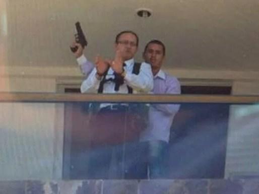Mensageiro do hotel algemado na varanda de um dos quartos com o sequestrador armado atrás  (Foto: Polícia Civil/Divulgação)