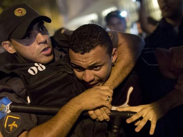 Policial detém manifestante em protesto no Rio de Janeiro nesta segunda-feira (12). (Foto: Felipe Dana/AP)