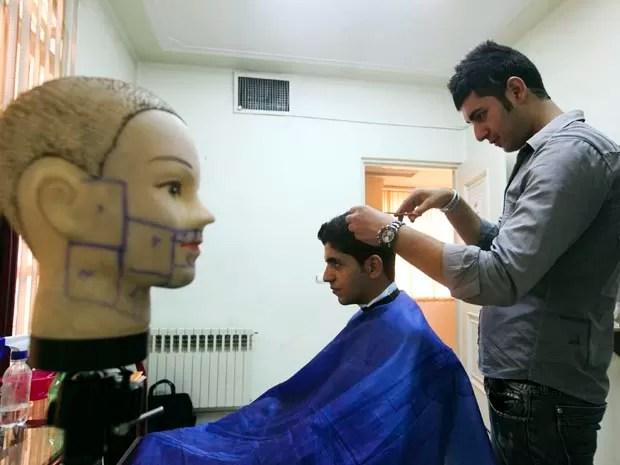 Barbeiro corta cabelo de freguês em salão oficial em Teerã nesta segunda (5). O Irã lançou um guia com modelos de corte de cabelo considerados apropriados para iranianos. (Foto: AP)