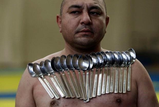 O georgiano Etibar Elchiyev posa com 53 colheres presas ao corpo em tentativa de recorde (Foto: David Mdzinarishvil/Reuters)