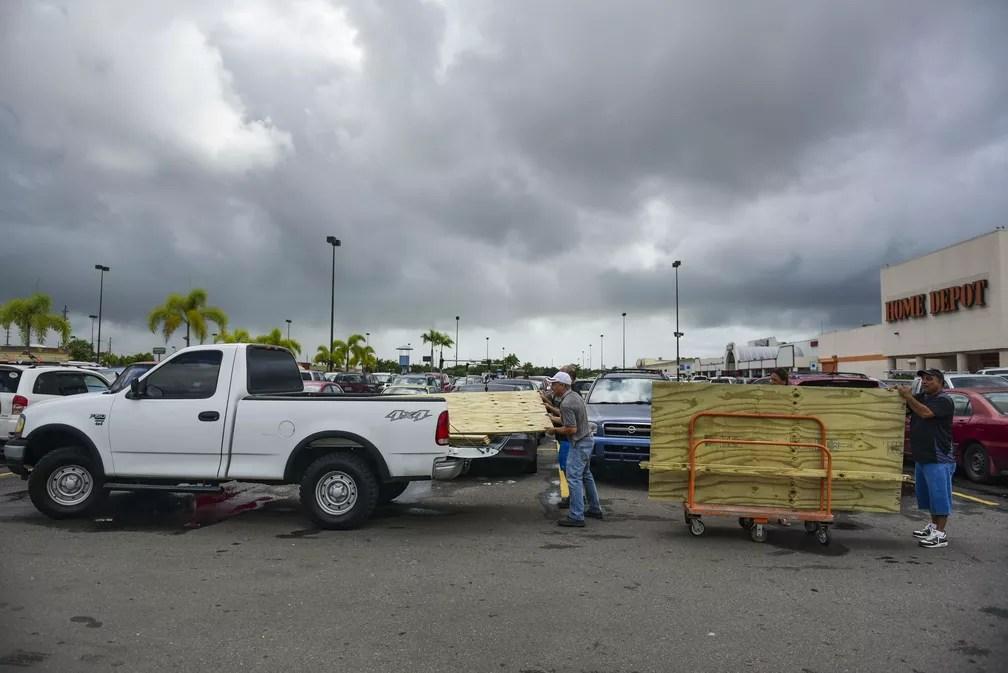 Homens carregam tábuas de madeira para proteger janelas antes da passagem do furacão Irma em Carolina, Porto Rico  (Foto: AP Foto/Carlos Giusti)